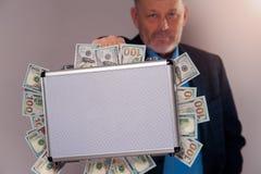 Homme supérieur tenant la serviette en métal avec des dollars Photographie stock