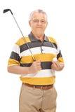 Homme supérieur tenant un club de golf et une boule Image stock