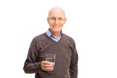 Homme supérieur tenant un verre de l'eau Images stock