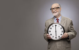 Homme supérieur tenant une grande horloge murale Image libre de droits