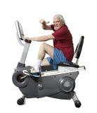 Homme supérieur tournant sur le vélo de forme physique d'isolement Photographie stock libre de droits
