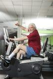 Homme supérieur tournant sur le vélo de forme physique dans le gymnase Images libres de droits