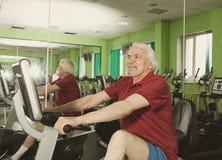 Homme supérieur tournant sur le vélo de forme physique dans le gymnase Photographie stock