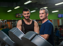 Homme supérieur travaillant avec l'entraîneur personnel dans le gymnase Photos stock