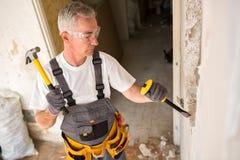 Homme supérieur travaillant avec le marteau et outil tandis que démolissez le mur Photo libre de droits