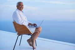 Homme supérieur travaillant sur l'ordinateur portable Photos stock