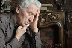 Homme supérieur triste posant à la maison Images libres de droits
