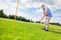 Homme supérieur visant à mettre une boule de golf dans le trou Images libres de droits