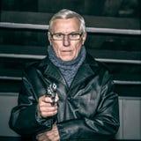 Homme supérieur visant une arme à feu Photographie stock
