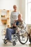 Homme sup?rieur dans le fauteuil roulant avec l'?pouse photo libre de droits