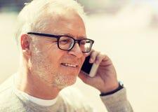Homme sup?rieur heureux invitant le smartphone dans la ville photo stock