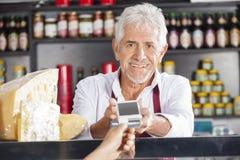 Homme supérieur acceptant le paiement du client dans la boutique de fromage Images stock