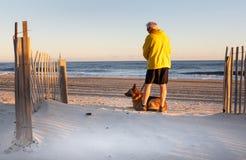 Homme supérieur avec le chien appréciant le matin sur la plage Photographie stock libre de droits