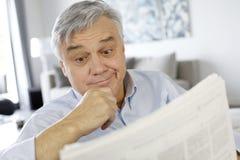 Homme supérieur avec le journal étonné de lecture de regard Photographie stock