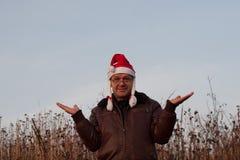 Homme supérieur dans le chapeau drôle de Santa avec des tresses avec les mains augmentées Photos stock