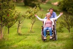 Homme supérieur poussant la femme dans le fauteuil roulant, nature verte d'automne Image libre de droits