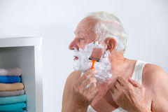 Homme supérieur rasant sa barbe Images stock