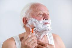 Homme supérieur rasant sa barbe Images libres de droits