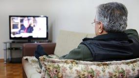 Homme supérieur regardant la TV Photo libre de droits