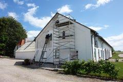 Homme sur des échafaudages peignant une maison Images stock