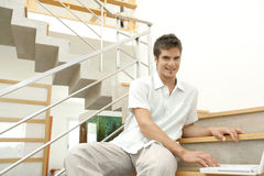 Homme sur des escaliers avec l'ordinateur portatif Image stock