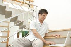 Homme sur des escaliers avec le sourire d'ordinateur portatif Photographie stock libre de droits