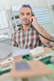 Homme sur des maisons de modèle de téléphone dans l'avant il Image libre de droits