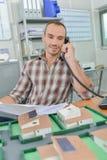 Homme sur des maisons de modèle de téléphone dans l'avant il Photos libres de droits