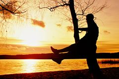 Homme sur l'arbre La silhouette de l'homme solitaire se reposent sur la branche de l'arbre de bouleau au coucher du soleil au riv Photo stock