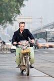 Homme sur l'e-vélo au centre de la ville, Pékin, Chine Photos stock