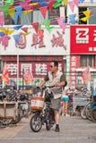 Homme sur l'e-vélo dans la zone d'atelier, Pékin, Chine Photos stock