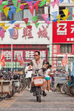 Homme sur l'e-vélo dans la zone d'atelier, Pékin, Chine Photographie stock