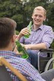 Homme sur la bière potable de fauteuil roulant avec l'ami Image stock