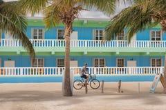 Homme sur la bicyclette devant l'hôtel dans le matoir de Caye à Belize Photographie stock libre de droits