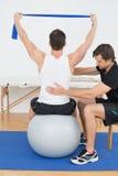 Homme sur la boule de yoga fonctionnant avec un physiothérapeute Photo libre de droits
