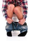Homme sur la cuvette des toilettes Photo stock