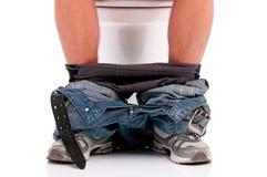 Homme sur la cuvette des toilettes Image libre de droits