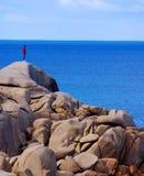 Homme sur la falaise rocheuse regardant au-dessus du bord Photographie stock libre de droits