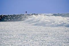 Homme sur la jetée de roche pendant la tempête Photographie stock