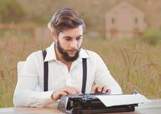 Homme sur la machine à écrire avec le fond mou de pays photo libre de droits