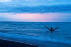 Homme sur la mer au coucher du soleil Image libre de droits