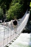 Homme sur la passerelle de suspension Photographie stock libre de droits