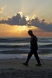 Homme sur la plage au coucher du soleil Photo stock