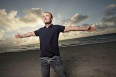 Homme sur la plage avec des bras étendus Image libre de droits