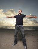 Homme sur la plage avec des bras étendus Photos stock