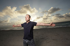 Homme sur la plage avec des bras étendus Images stock