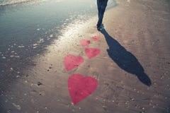 Homme sur la plage ensoleillée avec des symboles illustrés de coeur Images libres de droits