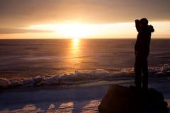 Homme sur la roche sur la mer dans la glace - silhouette Photo libre de droits