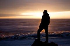 Homme sur la roche sur la mer dans la glace - silhouette Photos libres de droits