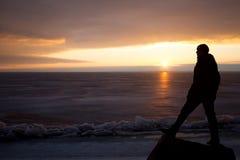 Homme sur la roche sur la mer dans la glace - silhouette Image libre de droits